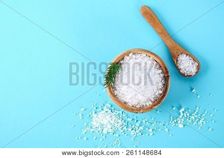 Crystals Of Large Sea Salt In A Wooden Bowl And Spoon And Dill On A Blue Table.