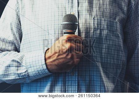 Public Speaker Holding Microphone, Low Key With Selective Focus
