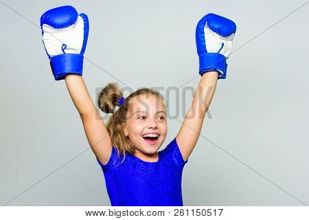 Girl Child Happy Winner With Boxing Gloves Posing On Grey Background. Feminist Movement. She Feels A