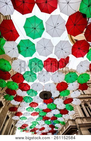 A lot of red white and green umbrellas hanging above the street