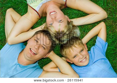 happy family three people on green grass