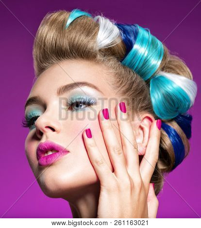 Fashion portrait of a beautiful woman with blue makeup and pink fingernails.  Beautiful fashion model. Gorgeous face of an attractive girl - pink background.  poster