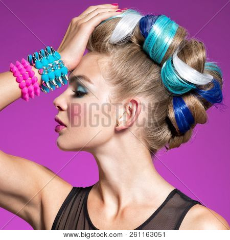 Fashion portrait of young caucasian model with bright makeup. Beautiful woman with creative hairstyle. woman with  Fashion make-up. Closeup portrait.  Portrait of a girl with bracelets on her hands