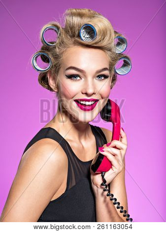Smiling girl with blue curlers talking by red telephone. Young happy woman with blue curlers calling by retro phone.  Portrain of an atractive female using a vintage phone.