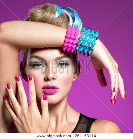 Fashion portrait of a beautiful woman with bright makeup. Closeup portrait. Gorgeous face of an attractive girl - pink background. Portrait of a girl with bracelets  thorns.