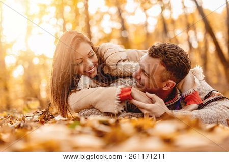 Beautiful Smiling Couple Enjoying In Sunny Forest In Autumn Colors. They Are Lying Down On The Fall
