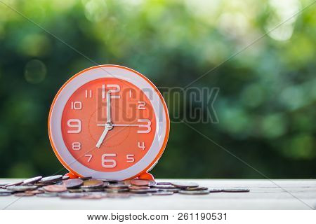 Time And Money Investment, Deadline Loan Money Concept : Time On Coins On Table With Green Bokeh As