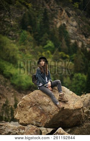 Young Lonely Tourist Cutie Girl Sitting On Stone On Shore Of River In Mountains In Wild Terrain And