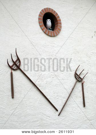 owl and old pitchforks on wall of swiss farm poster