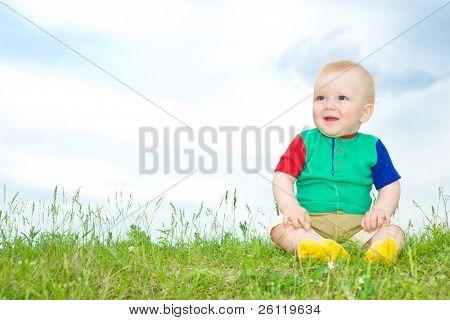 little baby sit on grass under blue sky