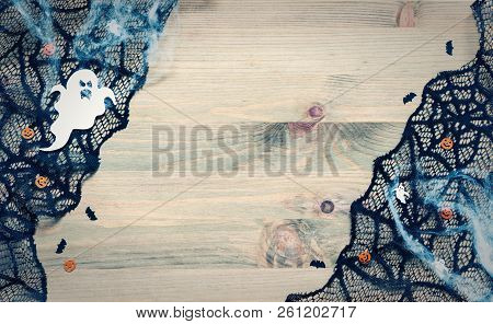 Halloween background. Spider web, cobweb lace and spooky ghosts decorations as the symbols of Halloween on the wooden background. Halloween composition