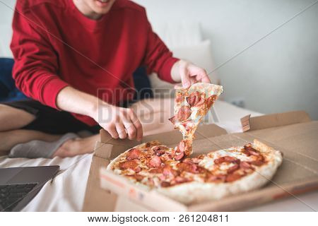 Young Man In A Red Sweatshirt Sits At Home On A Bed And Takes An Appetizing Piece Of Pizza From The