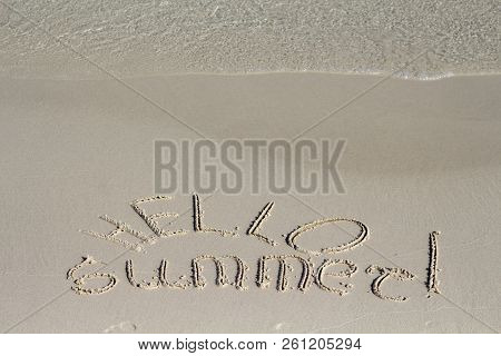 Hello Summer Inscription On Sand Beach Background. Sunny Beach Sand Message With Sea Wave. Hello Sum
