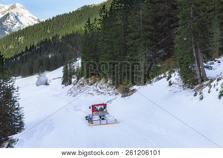 Snowy Peaks Of The Alps Mountains, Evergreen Fir Forest And A Snowcat Going Through Snow, In Decembe