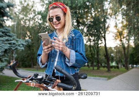 Happy, Stylish Girl Sitting On A Bike In The Park, Using A Smartphone And Smiling. Walk On The Bike