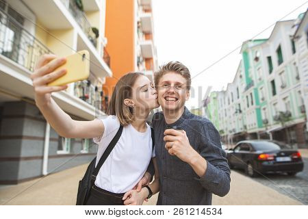 Portrait Of A Happy Young Couple: Girl Kisses Her Boyfriend In A Cheek And Takes A Selfie On A Smart