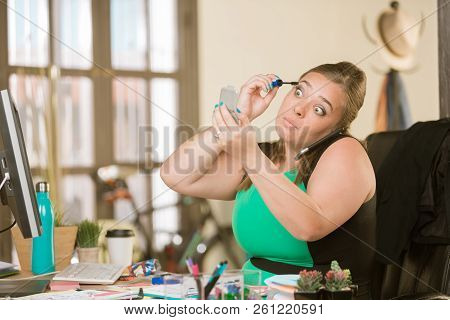 Pretty Young Woman Applying Mascara At Her Desk While On A Call