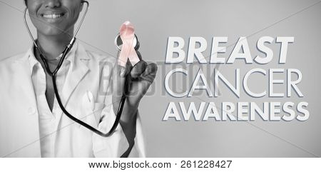 Breast cancer awareness message against smiling nurse holding pink ribbon breast cancer awareness