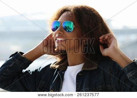 pretty woman wearing sunglasses with perfect teeth and dark clean skin having rest outdoors, smiling after received good positive news. Beautiful young dark-skinned female enjoy nature.