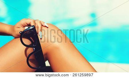 Beautiful Young Slim Woman Legs Sunbathe Near Swimming Pool. Sunglasses, Women's Legs Resting In Swi