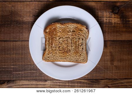 Toast on white plate and wooden table