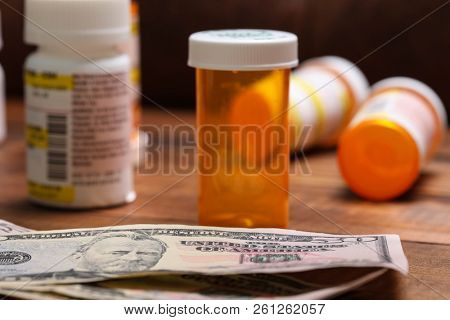 Pills bottles and money on table