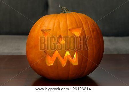 Orange pumpkin head on table