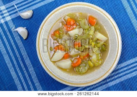 Leek soup with potato on blue background with garlic