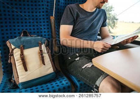 A Tourist Sits By The Window In A Train Or Commuter Train And Looks At A Map.