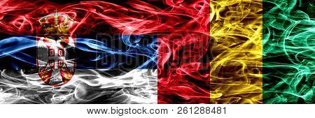 Serbia Vs Guinea, Guinean Smoke Flags Placed Side By Side. Thick Colored Silky Smoke Flags Of Serbia