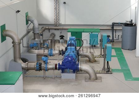 Large Industrial Water Treatment Boiler Room Steel Metal Pipes And Blue Pumps And Valves