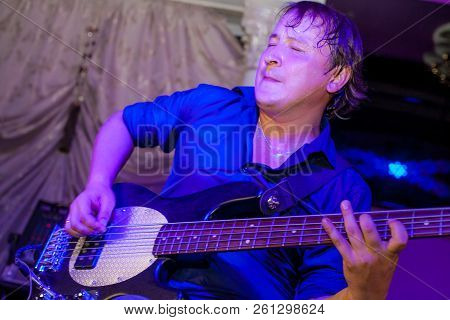 Musician Plays Bass Guitar On Stage In Neon Light