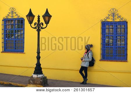 Female Leaning Against Vivid Yellow Rough Wall With Vivid Blue Artistic Windows And A Vintage Gorgeo