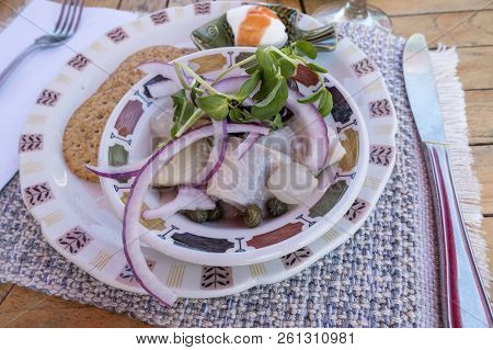 Pickled Herrings Served With Red Onions, Pea Sprouts, Pickled Pearl Onions And Capers In A Colorful