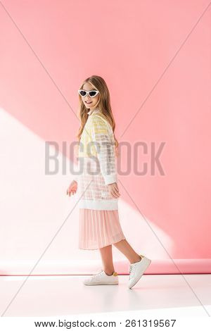 adorable stylish female youngster posing in elegant clothes and sunglasses on pink poster