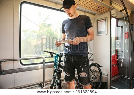 A Cyclist Or A Tourist Next To A Bike At A Special Place For Transporting Bicycles On A Train Looks