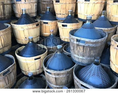 Wine Carboys Bottles Enclosed In Wickerwork Outside At Farm