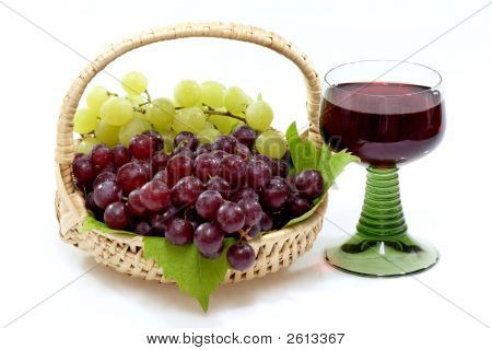 Red wine and grapes in a basket on bright Background. Shot in Studio. poster
