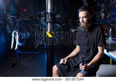 Portrait Of Small Business Owner Of Young Man With Beard. Guy Bicycle Mechanic Workshop Worker Sitti