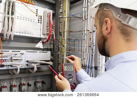 Engineer Electrician With Multimeter In Electrical Control Box Tests Equipment. Maintenance Of Elect