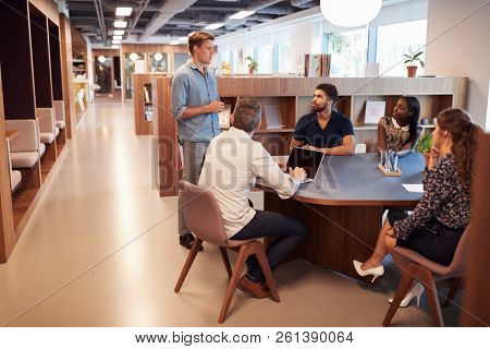 Casually Dressed Businessmen And Businesswomen Having Informal Meeting In Modern Office