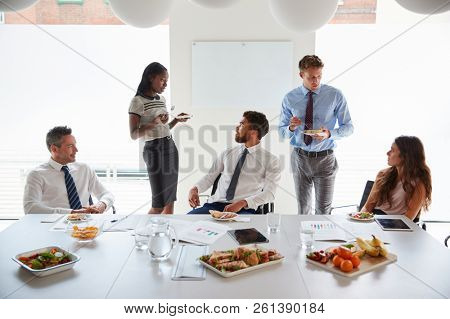 Businessmen And Businesswomen Meeting In Modern Boardroom Over Working Lunch poster
