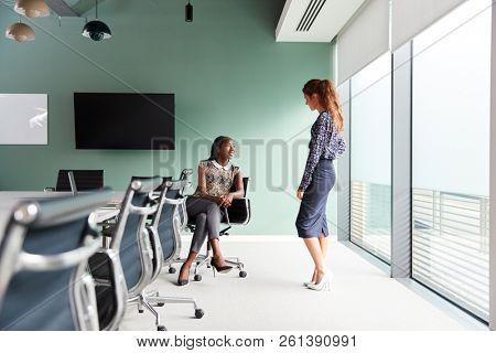 Casually Dressed Businesswomen Having Informal Meeting In Modern Boardroom