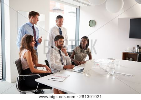 Businessmen And Businesswomen Meeting Around Table In Modern Boardroom