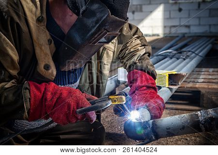 Close Up Welder Weld Metal Pipe At Construction Site. A  Builder In Brown Uniform, Welding Mask And