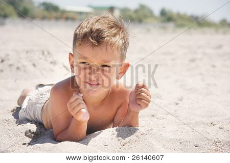 young boy laying on sand beach