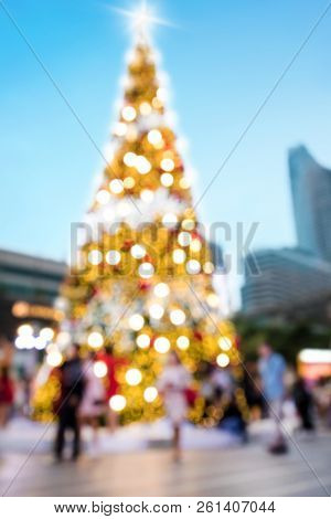 Conceptual defocused abstract decorated Christmas Tree and crowd of people on city street at night