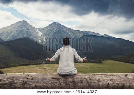 Young African Americans Guy Sitting On A Big Log With Hands Apart And Looking At The Beautiful Panor