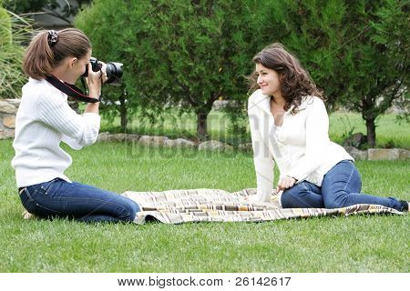 two young women taking pictures on natural background