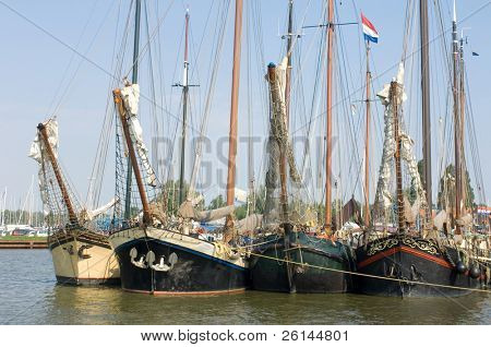 A row of old sailing vessels, neatly arranged in the harbor poster